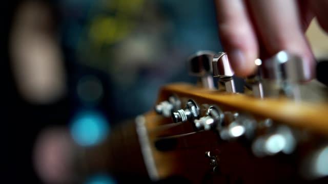 vídeos de stock e filmes b-roll de tuning guitar - instrumento musical