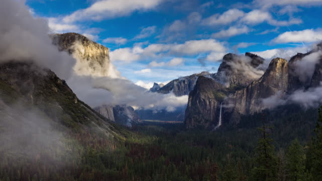 Tunnel View on Foggy Winter Day - Time Lapse Time lapse clip of the famous Tunnel View in Yosemite National Park, where a wintry fog is slowly dispersing to reveal the landmarks and blue sky. national landmark stock videos & royalty-free footage