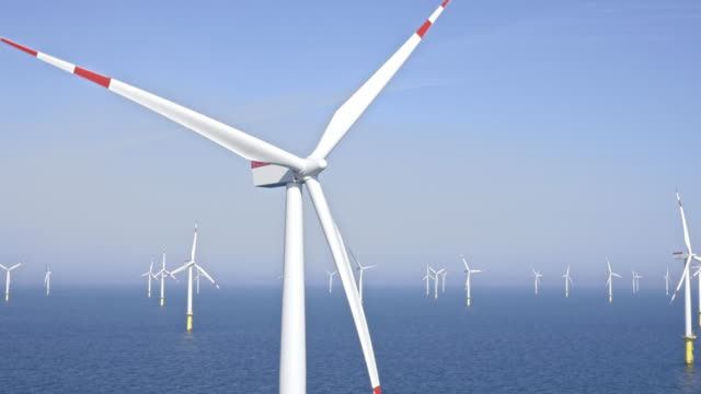 aerial turbine at offshore wind farm shining in the sun - turbina a vento video stock e b–roll