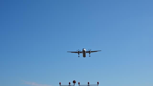 4k turboprop plan landning flygande overhead - liten bildbanksvideor och videomaterial från bakom kulisserna
