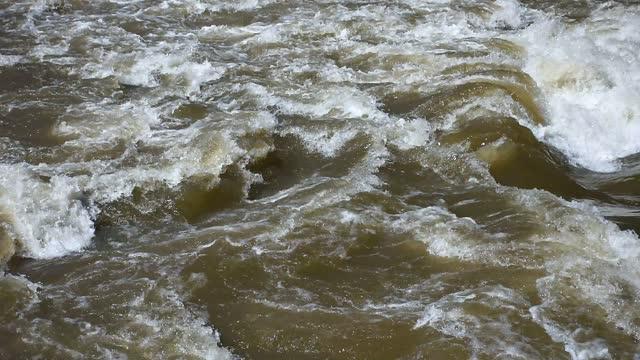 vidéos et rushes de eau turbulente jaillissante de fleuve, écoulement vertigineux, vagues d'eau mousseuse tourbillonnantes après de fortes pluies, rapides turbides d'eau de fleuve de mur, autriche - marron couleur