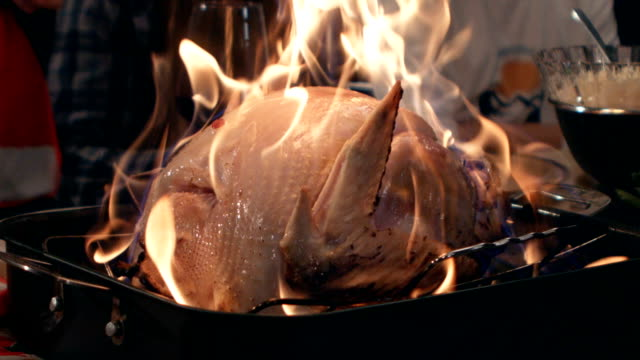 vídeos de stock e filmes b-roll de a turkey is lit on fire for the holidays - christmas cooking