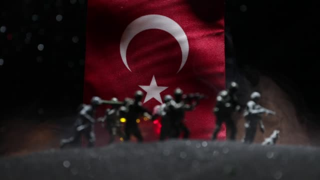 Turkish army concept. Silhouette of armed soldiers against a Turkish flag. Creative artwork decoration. Military silhouettes fighting scene dark toned foggy background. Selective focus