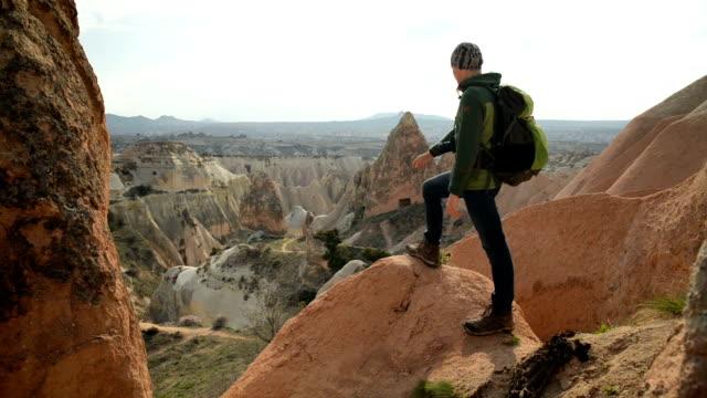 stockvideo's en b-roll-footage met turkse cappadocië rock formatie landschap waargenomen door toerist - geologie