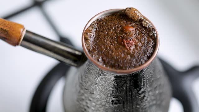 Turkish coffee in copper cezve at gas stove.