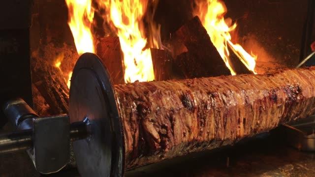 türkischer doner kebab dreht sich um grill, lokale lebensmittel, street food truthahn, kebab truthahn, rindfleisch, steak-restaurant, flammen, holzfeuer kebab - döner stock-videos und b-roll-filmmaterial