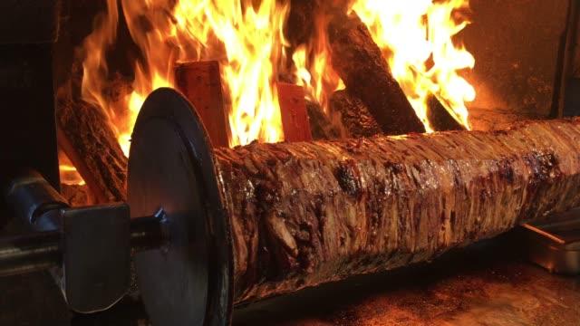 türkischer doner kebab, doner kebab mit flammen, brennholz, kochen türkischer kebab in holzfeuer, kebab roll, traditionelles türkisches essen - döner stock-videos und b-roll-filmmaterial