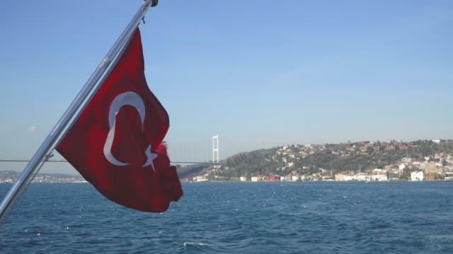 turkish flag waving on a boat in bosphorus strait, istanbul, turkey - państwo lokalizacja geograficzna filmów i materiałów b-roll