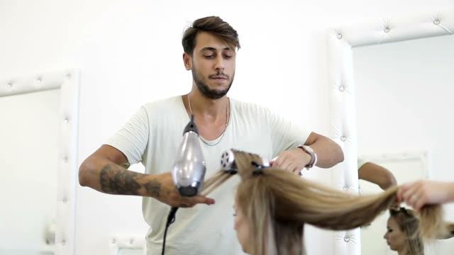 türkischer mann friseur stylist trocknet lange weibliche fön. - haartönung stock-videos und b-roll-filmmaterial