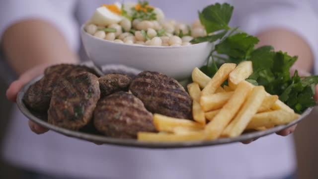 vídeos de stock e filmes b-roll de turkish meatball and piyaz on a plate - produto de carne