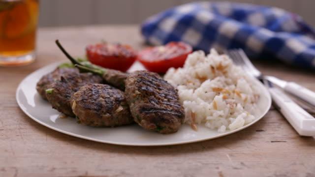 vídeos de stock e filmes b-roll de turkish meatball and rice on a plate - produto de carne
