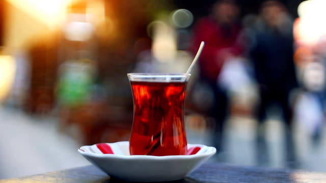 Turkish tea with special cup on a sidewalk tea house table with unrecognizable blurry people on the background Black tea with special Turkish tea cup on a sidewalk tea house table with unrecognizable blurry people on the background turkish culture stock videos & royalty-free footage