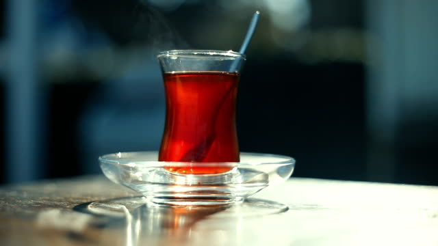 Turkish tea with special cup on a sidewalk tea house table with unrecognizable blurry people on the background video