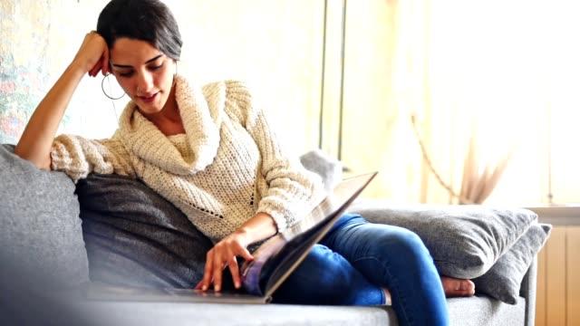 stockvideo's en b-roll-footage met turkse vrouw lezen van een tijdschrift op de bank - woman home magazine