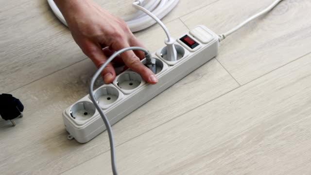 vidéos et rushes de éteignez la bande de néon et débranchez la prise du protecteur de surtension du cordon d'extension - vidéos de rallonge électrique