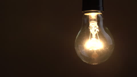 Turn on and turn off a incandescent bulb Close up shot of Turn on and turn off a incandescent bulb with copy space in dark room, Old style technology with copy space igniting stock videos & royalty-free footage