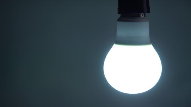 ein- und ausschalten einer led-glühbirne - led leuchtmittel stock-videos und b-roll-filmmaterial