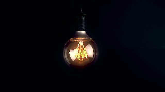 オンにしをオフに点滅効果を持つ led 技術とレトロなビンテージ電球温かみのある明るい黄色の色合いと黒の背景の組み込み - 電球点の映像素材/bロール