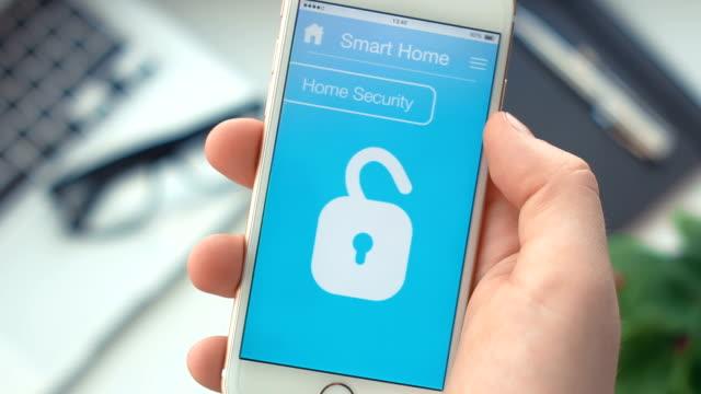 stockvideo's en b-roll-footage met schakel huis beveiliging in op de smart home-app op de smartphone - alarm, home,