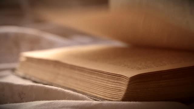 turn over sheets an old vintage book close-up lying on a flat surface - szpatułka przybór do gotowania filmów i materiałów b-roll
