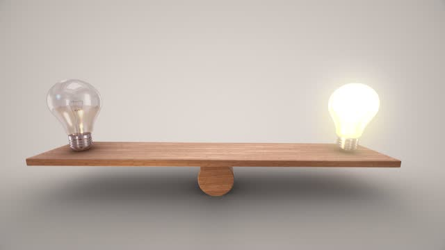 Turned on and off light bulb balancing on a wooden seesaw. Animation slows down on both sides. You can stop on the side you choose. The concepts of success idea leadership marketing planning solution finance business inspiration time brainstorming