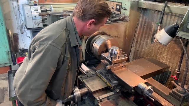 turner behind a turning and milling machine. - poliuretano polimero video stock e b–roll