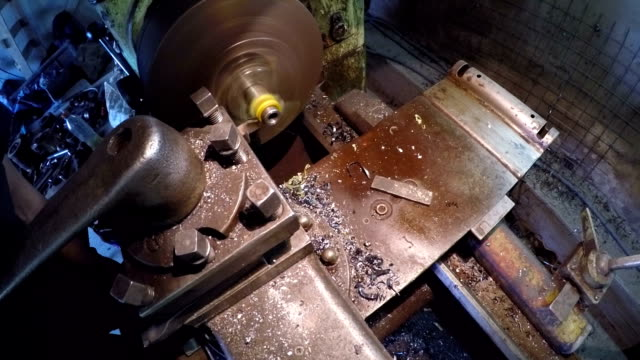 Turner Grinding Plastic Bushing CLOSE UP: Slow motion of a turner working at workshop grinding plastic bushing while making it using special machine-tool which stops spinning. anvil stock videos & royalty-free footage