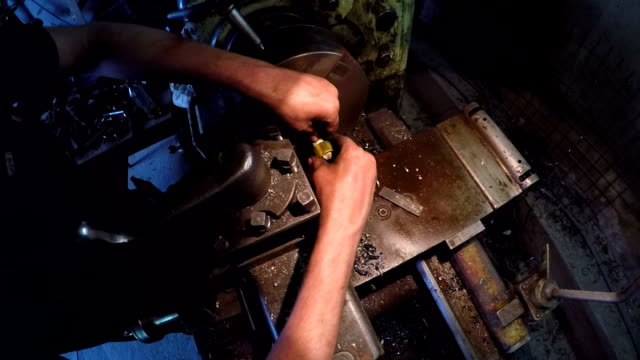 Turner Making Plastic Plug On Machine CLOSE UP: Slow motion view of a turner illuminated hands making a small yellow plastic plug with hands fixing it on a special machine-tool. anvil stock videos & royalty-free footage