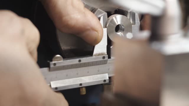 Turner Measures with a Caliper Part in a Lathe. video