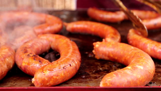 turning delicious juicy sausages on steel barbecue plate with handle. - pinze attrezzo manuale video stock e b–roll