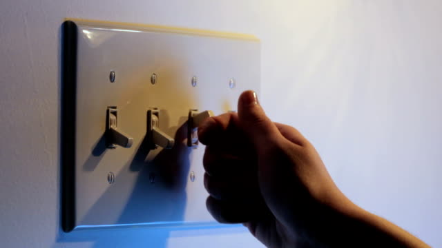 Turning light switches on and off HD video of multiple light switches being turned on and off, one at a time, with light getting progressively brighter and darker start button stock videos & royalty-free footage