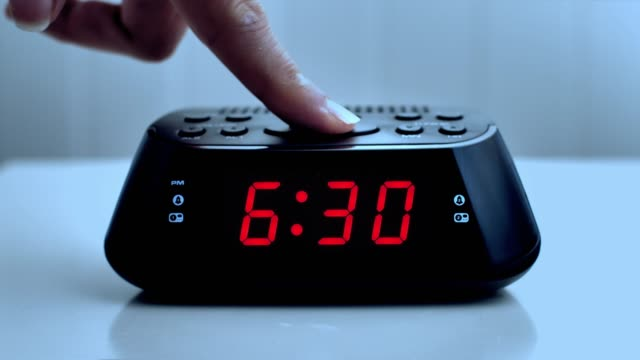 Turning off a digital alarm clock, time from 6.29 to 6.30. Woman's hand.