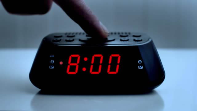 Turning off a digital alarm clock, time from 7.59 to 8.00.