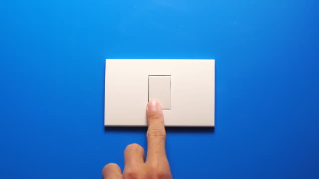 Turning off light bulb switch on blue wall 4k real time of People turning off light bulb switch on blue wall background with copy space. save energy and global warming concept start button stock videos & royalty-free footage