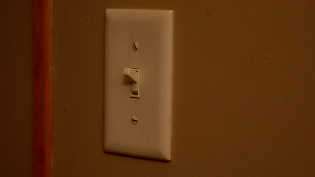 Turning On and Off Light Switch Close up of a female hand turning on and off the light switch. start button stock videos & royalty-free footage