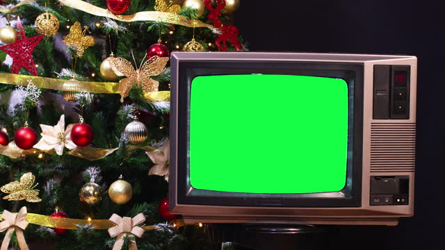 Turning on vintage tv with green screen in front of Christmas tree