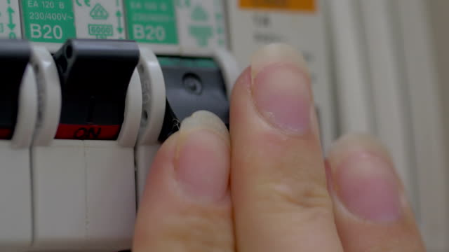 Turning on water heater on power panel Close-up shot of woman hand switching on the hot-water heater on home power panel, indicator turns red. Energy saving futebol stock videos & royalty-free footage