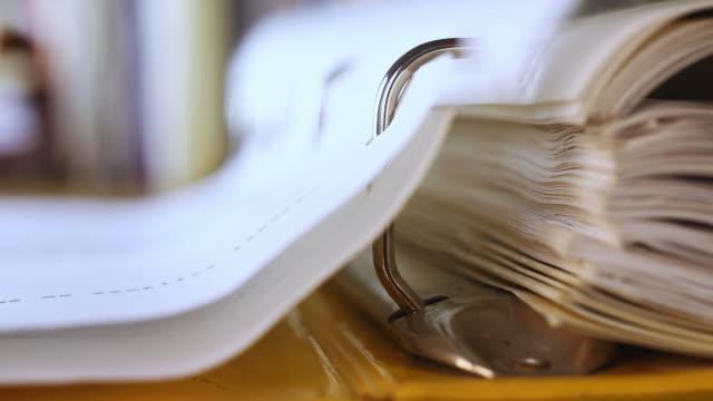 vídeos de stock e filmes b-roll de turning pages of a binder - dossier