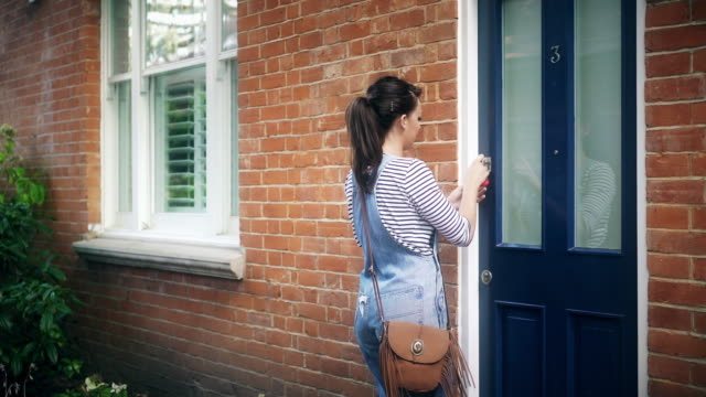 Turning the key, opening the front door. video
