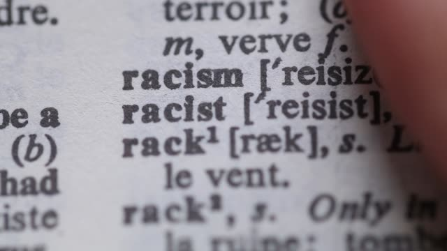 Turning the pages of a dictionary on the word RACISM video