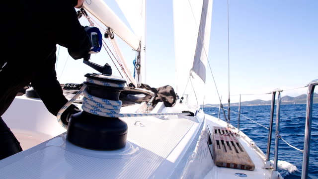 SLO MO Turning The Winch Handle On A Boat HD1080p: SLOW MOTION CLOSE UP shot of a man turning the winch handle while tightening a rope around a winch on a sailboat sailing on the ocean. regatta stock videos & royalty-free footage