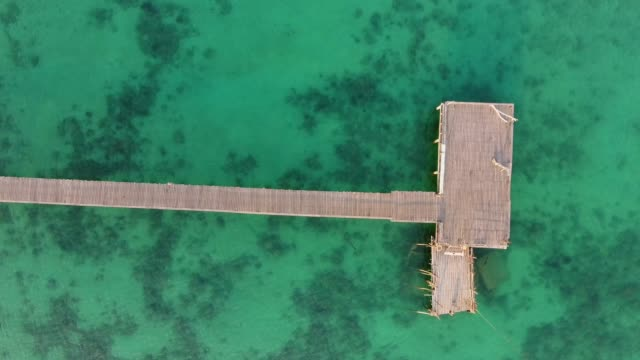 Turquoise Ocean with Long Wooden Jetty at Sunrise, Aerial Top View