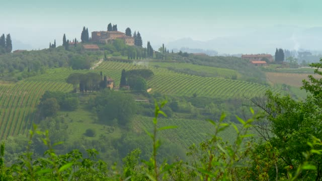 Tuscany, Italy. Typical tuscan region farm house, hills and vineyard.