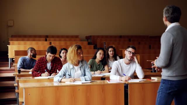 家庭教師は、カジュアルな服装の若者たちが質問を求めている広々 とした大学講義室の机で座っている学生に話しています。教育と大学のコンセプトです。 ビデオ