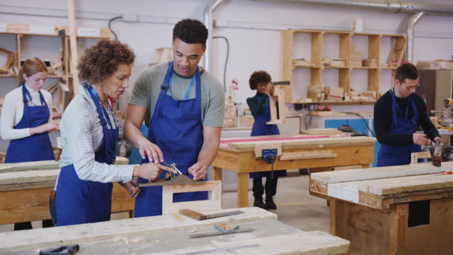 Tutor With Carpentry Student In Workshop Studying For Apprenticeship At College Using Wood Plane