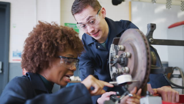 Tutor With Female Students Checking Car Brake Discs On Auto Mechanic Course At College