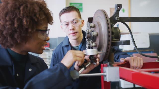 преподаватель с женщинами-студентами проверка автомобильных тормозных дисков на автомеханик курс в колледже - моторное транспортное средство стоковые видео и кадры b-roll