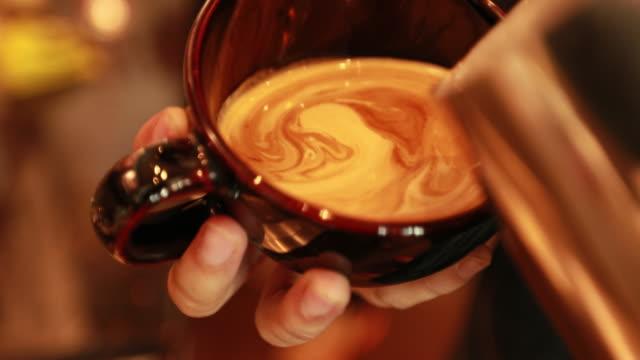 vídeos de stock e filmes b-roll de tutorial barista making art latte - triturar atividade