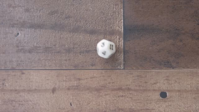 Twelve sided dice rolls and lands on a ten. on wood background. closeup.