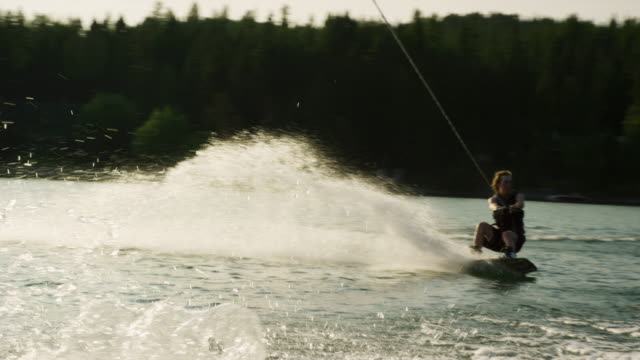 A Twenty-Something Caucasian Male Jumps and Performs Tricks on a Wakeboard before Falling on Glen Lake near Victor, Montana on a Sunny Afternoon